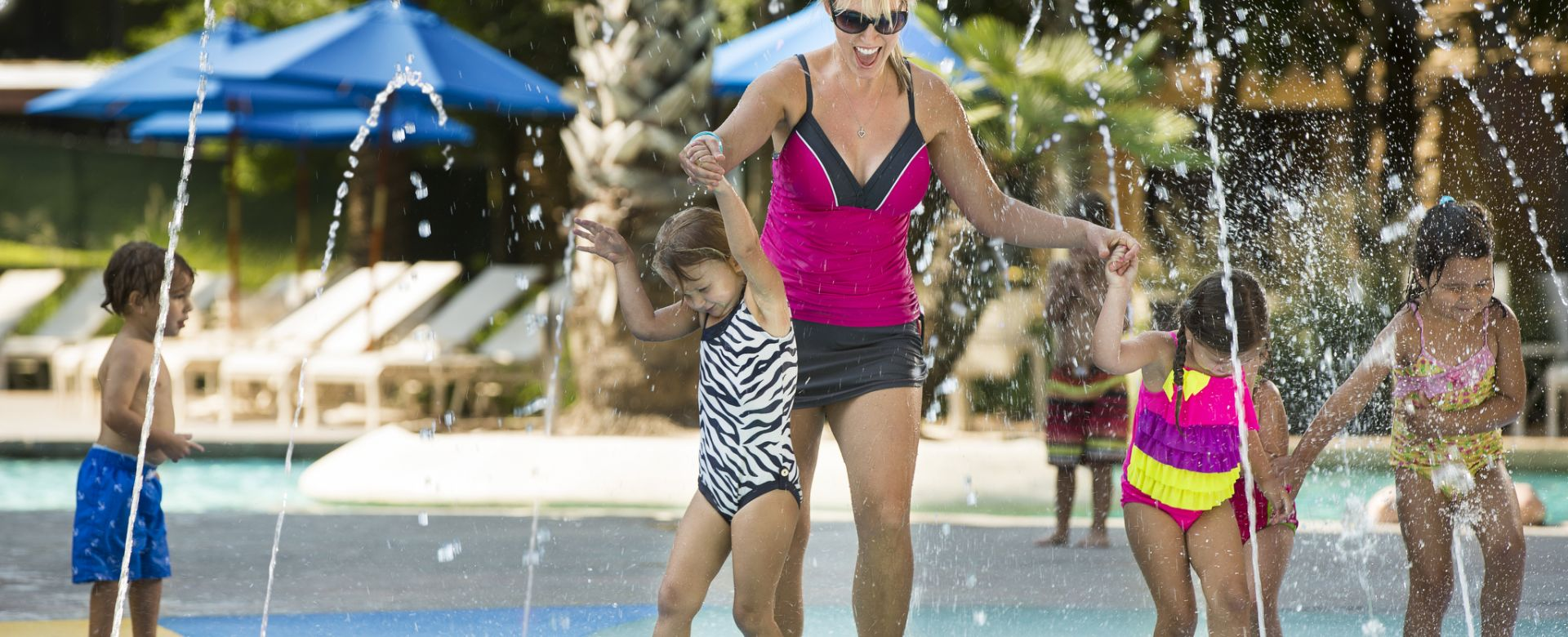 Woman playing on a splash pad with her kids