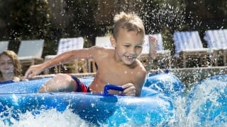 Boy splashing around in a tube in the lazy river
