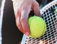 Man holding ball against racquet, about to serve