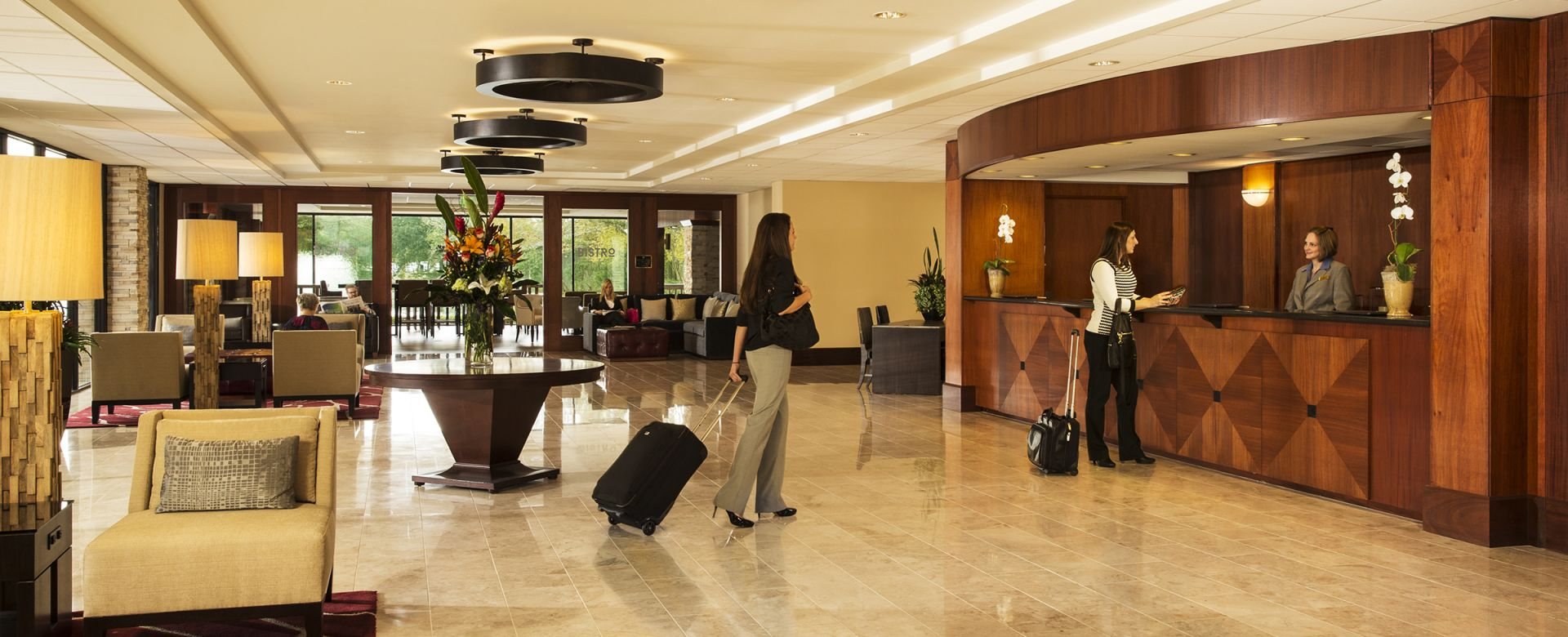 Woman approaching the front desk inside the Woodlands Resort lobby
