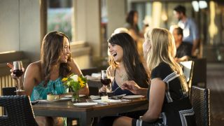 Young women laughing over dinner on the patio