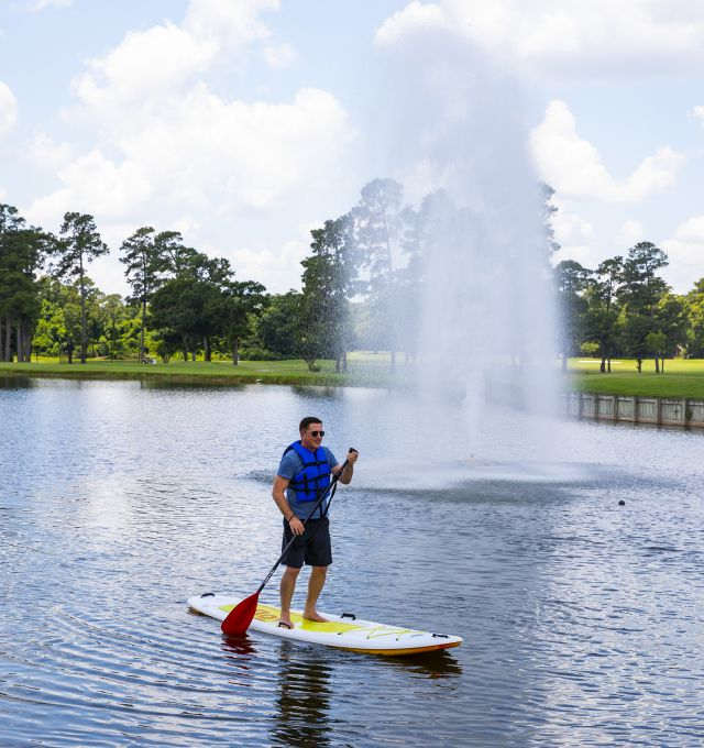 A man paddle-boarding by a fountain