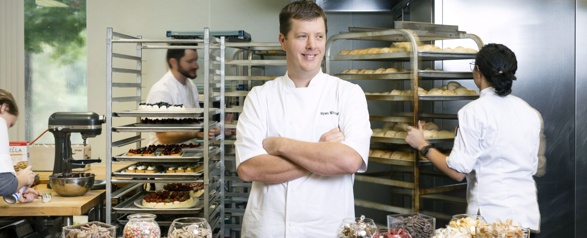 A chef smiles behind a display of macarons and chocolates.
