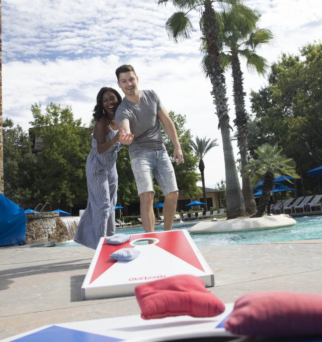 A couple play a bean bag toss game by the pool.