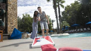 A couple playing a bean bag toss game together.