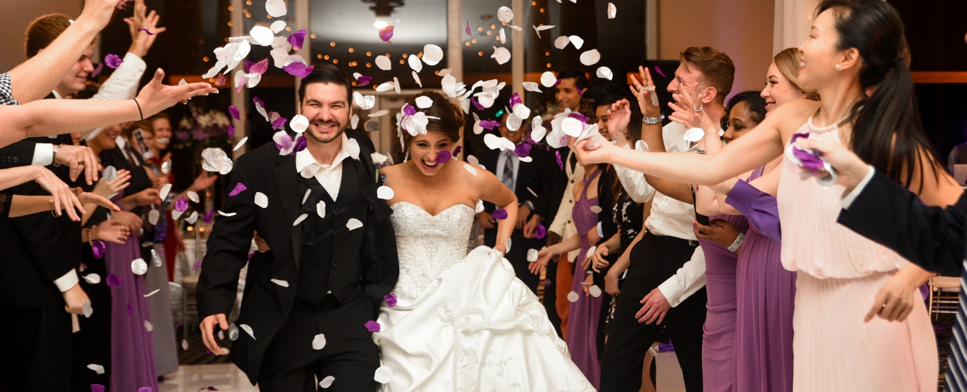 A groom and bride are showered with white and purple petals.
