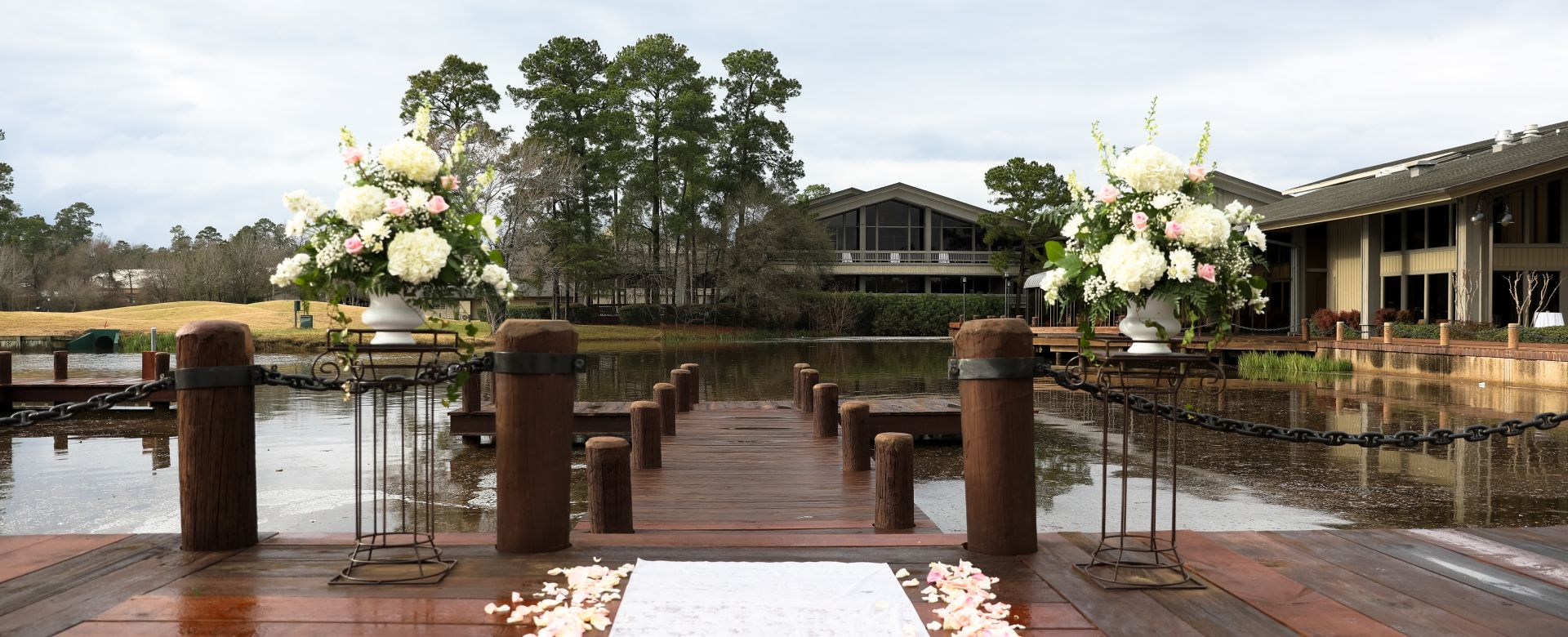 A wedding aisle lined with white petals on a wooden dock.