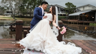 A groom and bride pose together on a dock next to the water.
