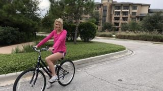 A lady on a bike poses in front of The Woodlands resort.