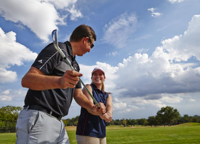 A golf instructor teaches a lady how to swing the club.