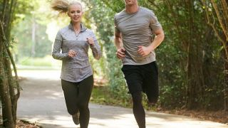 A couple jog together along a paved forest path.