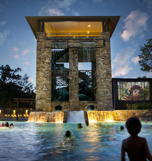 A movie plays on a large screen next to an outdoor pool.