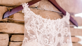 A white wedding dress on a hanger.