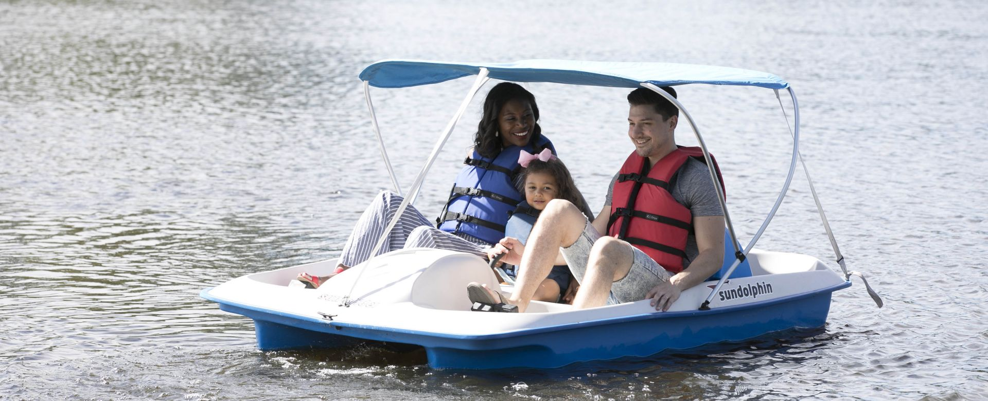 A family paddle-boating on a lake.