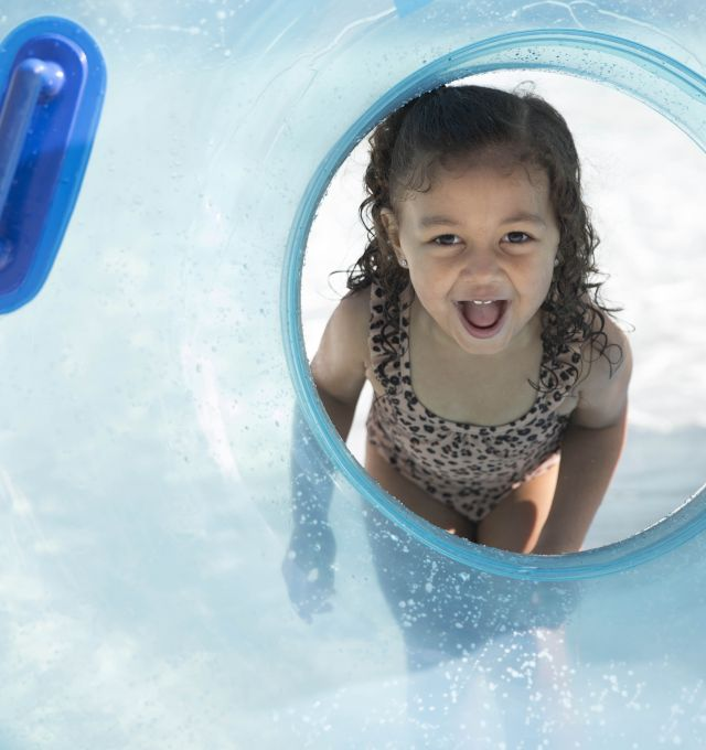 A girl stick her head in the hole of a blue water tube.