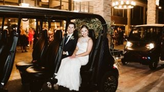 A groom and bride ride in a black golf cart.