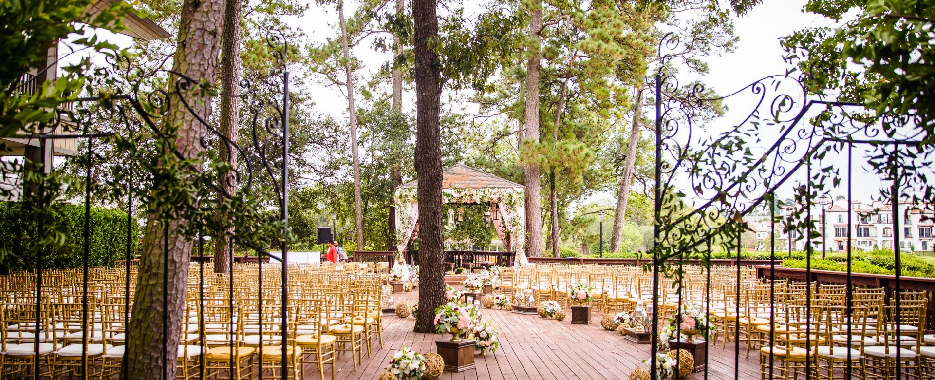 A large deck with chairs and an aisle decorated for a wedding ceremony.