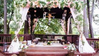 A pavilion decorated with hanging lanterns, pink curtains and flowers.