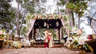 A bride and groom stand together under a decorated pavilion.