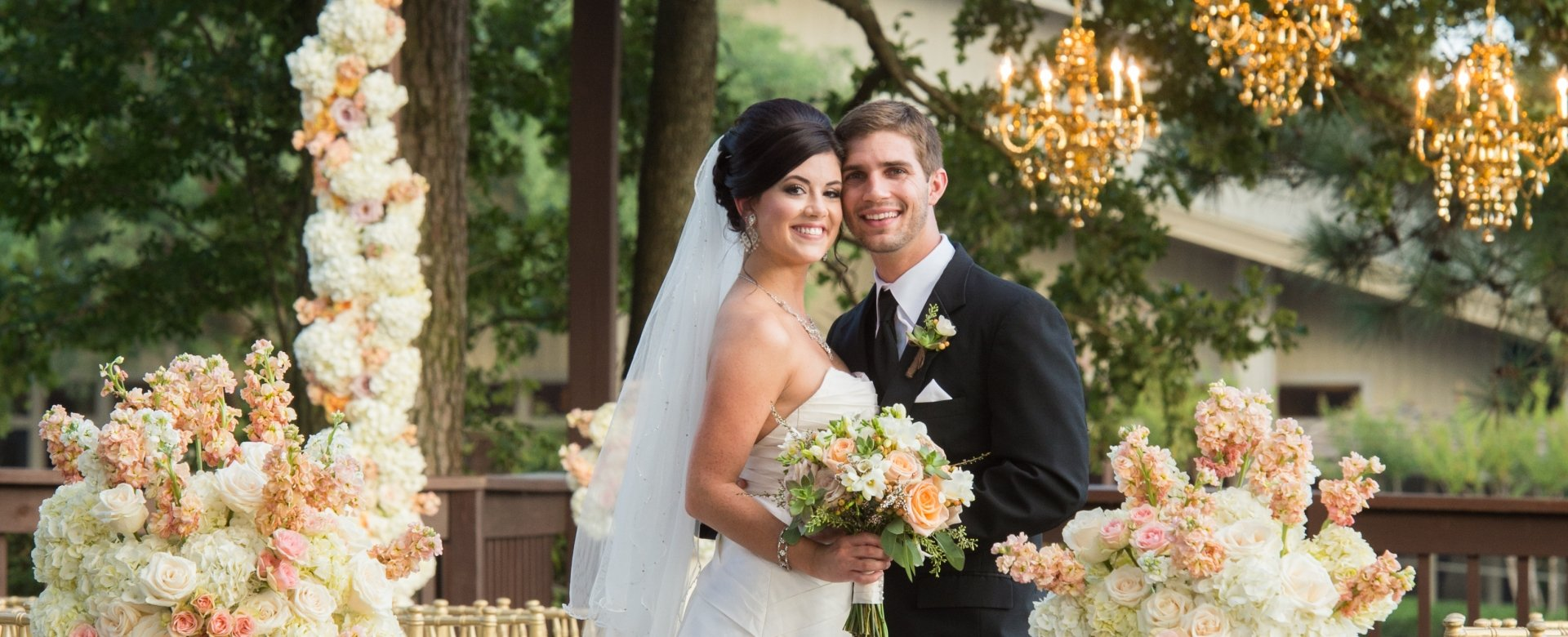 A groom and bride smile while standing under a decorated pavilion.