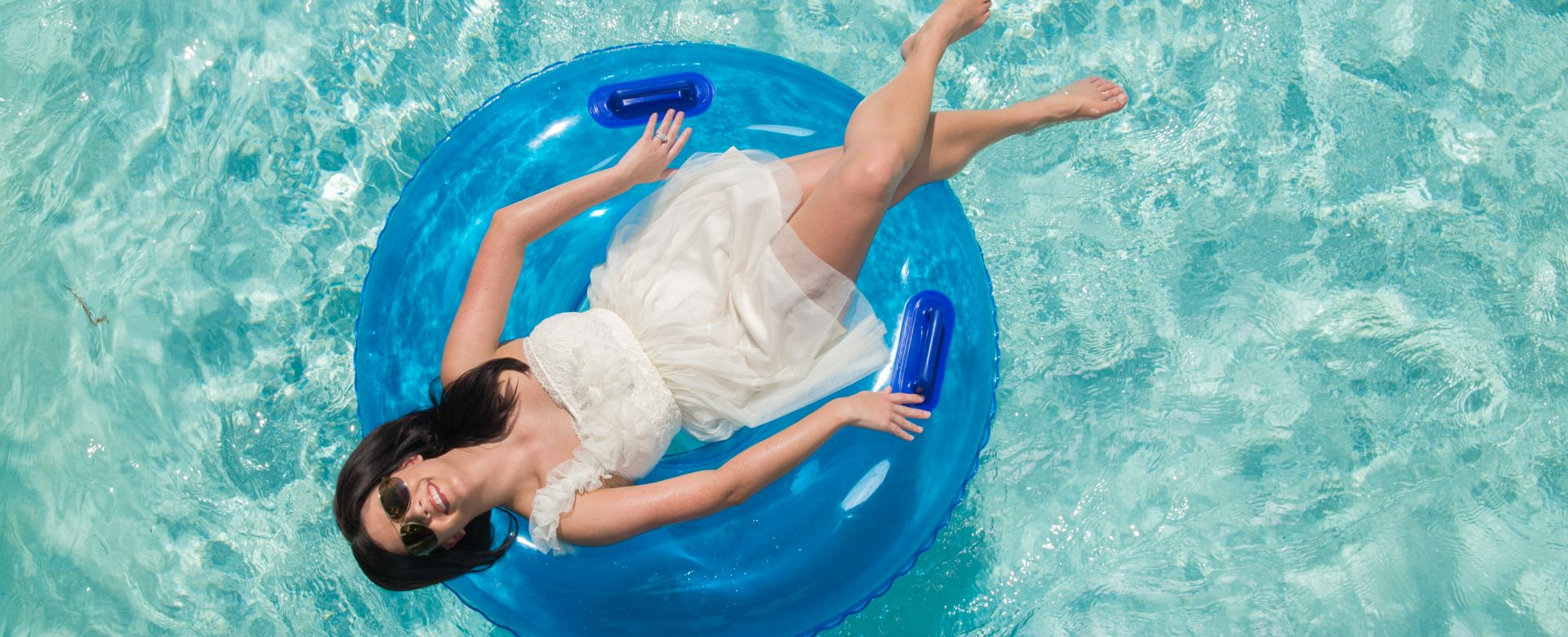 A woman wearing a white dress relaxes in a water tube.