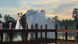 A groom and bride stand together on a wooden dock.