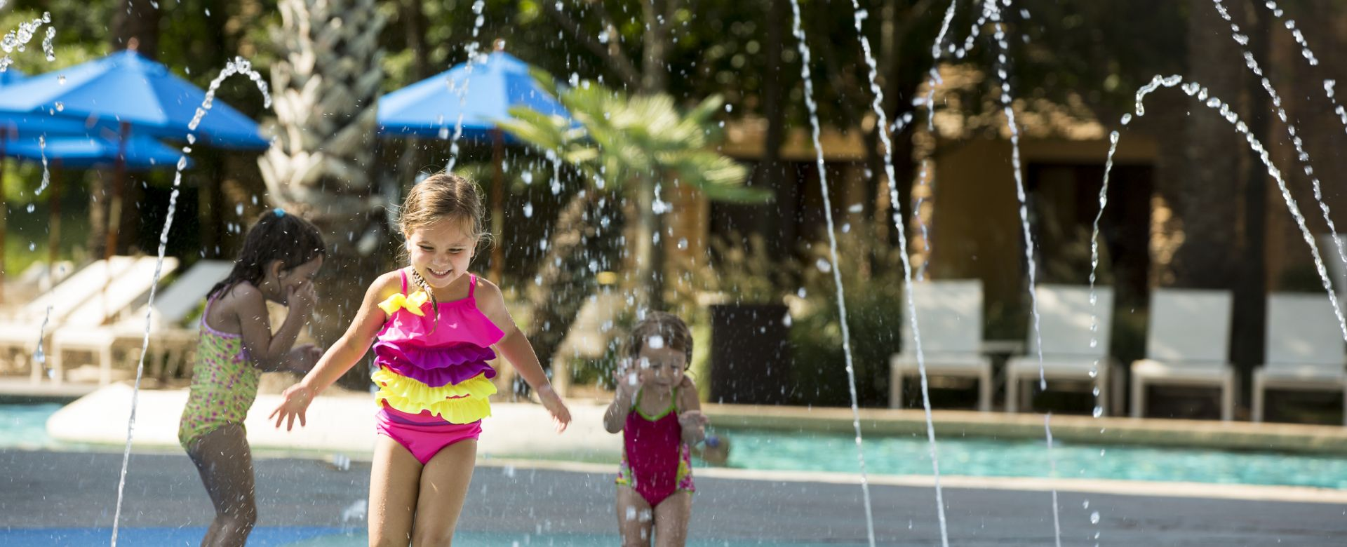 Kids smile and run through streams of water at a outdoor pool.