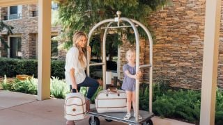 A mother and daughter load their bags onto a luggage cart.