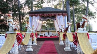 Statues of Ganesha line the aisle of an outdoor wedding ceremony.
