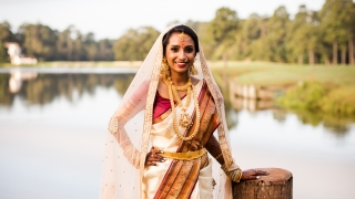 A woman wearing a traditional Indian wedding dress poses on a dock.