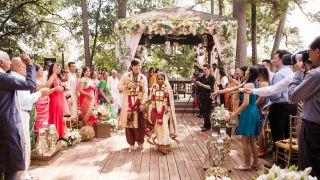 A bride and groom in traditional Indian clothing walk down the aisle while people throw white petals.