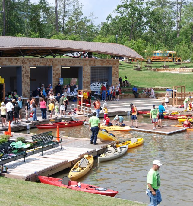 People wait in line at a busy boat club on the shore of a lake.