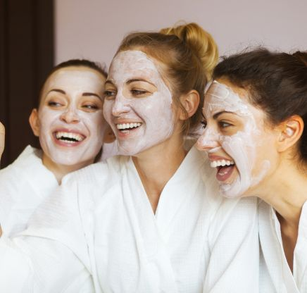 3 women with white facials smile for a photo.