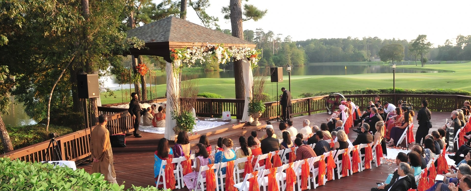 An outdoor wedding ceremony next to a golf course.