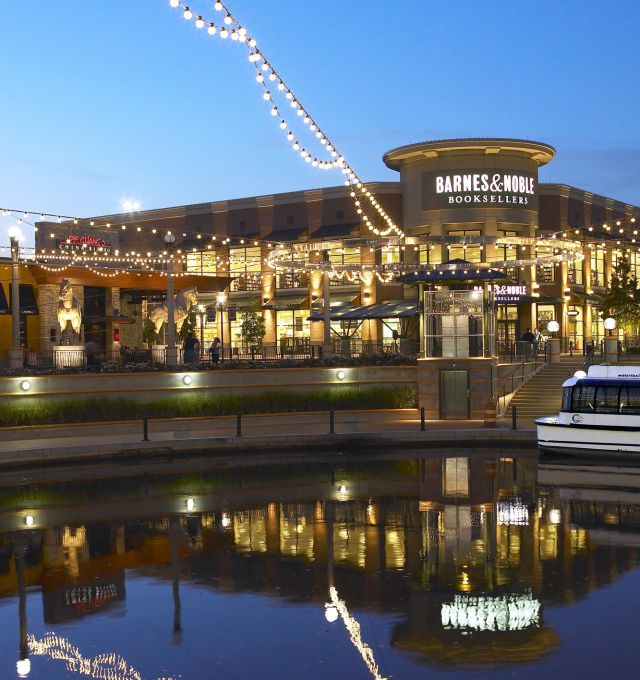 Strings of lights hang above a small pond in a shopping plaza.
