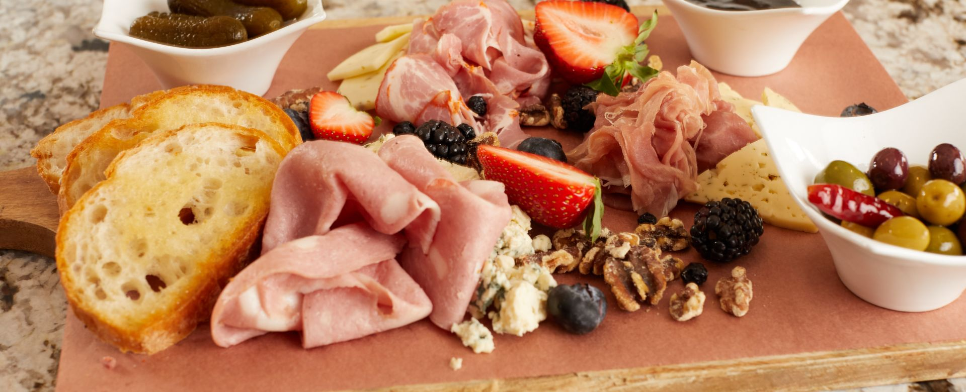 A bread, prosciutto, fruit and cheese tray.