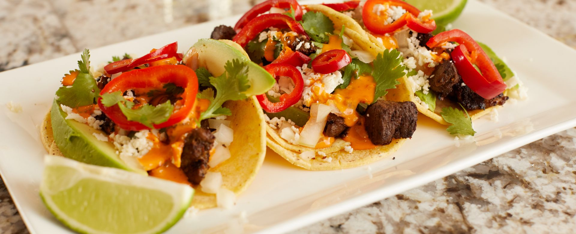Soft shell tacos with avocado, lime and peppers.