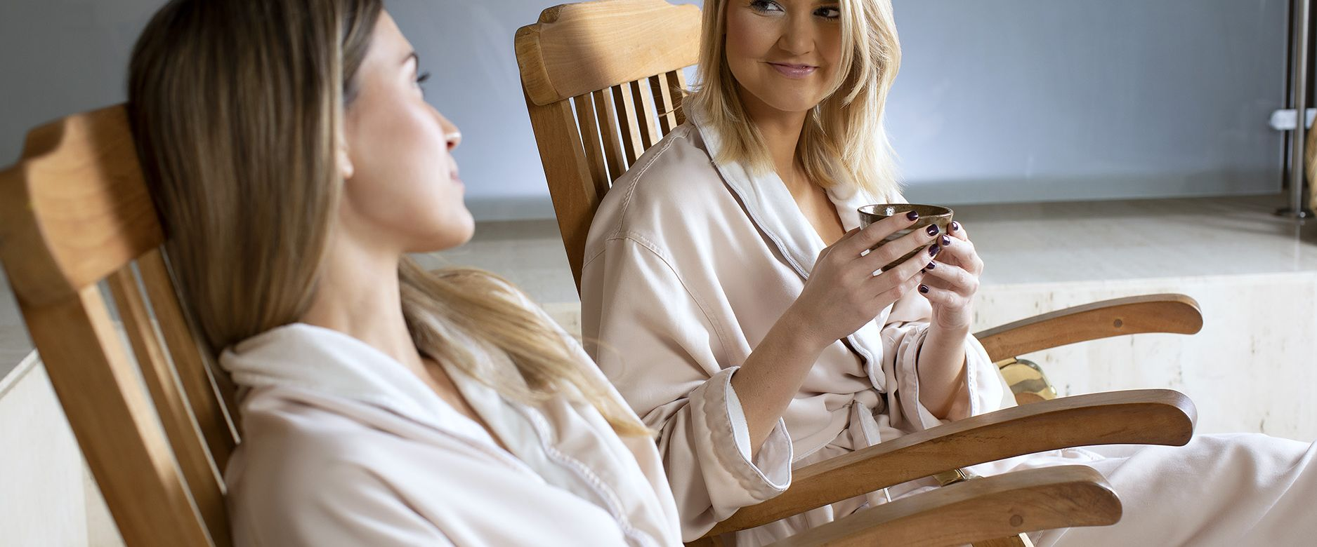 Two ladies chat and relax in wooden spa chairs