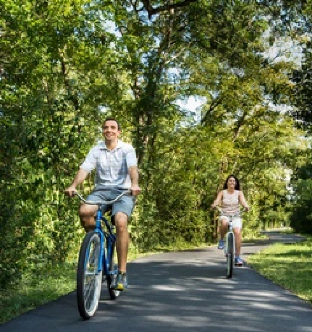 Couple riding bicycles down a path
