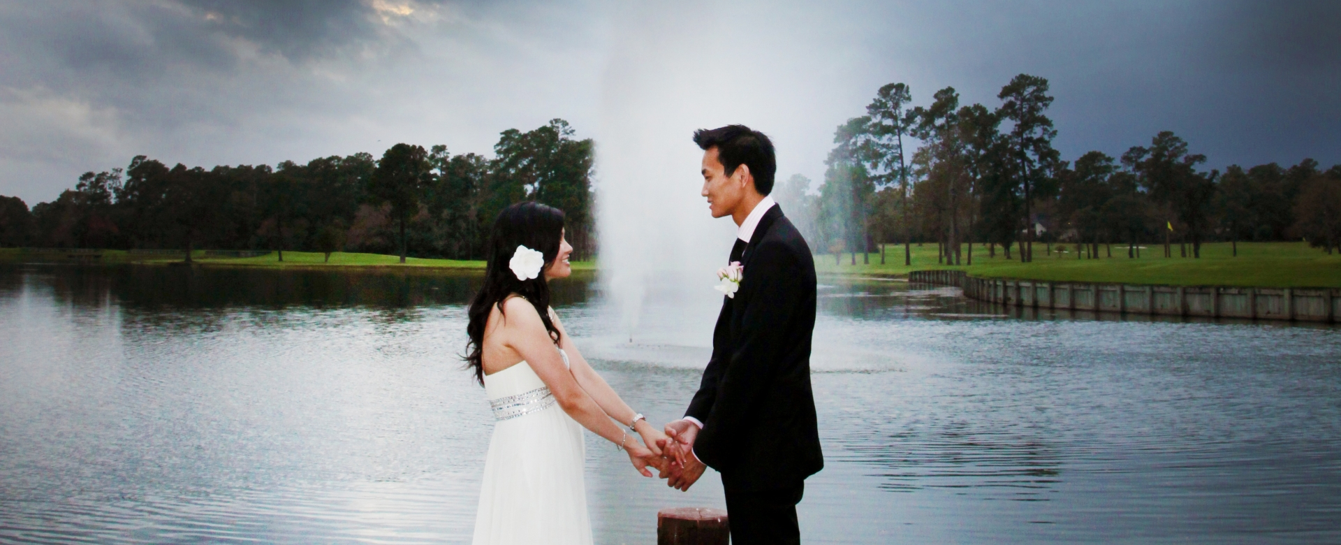 A bride and groom hold hands on the edge of a wooden dock.