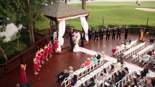 An outdoor wedding ceremony next to golf course.