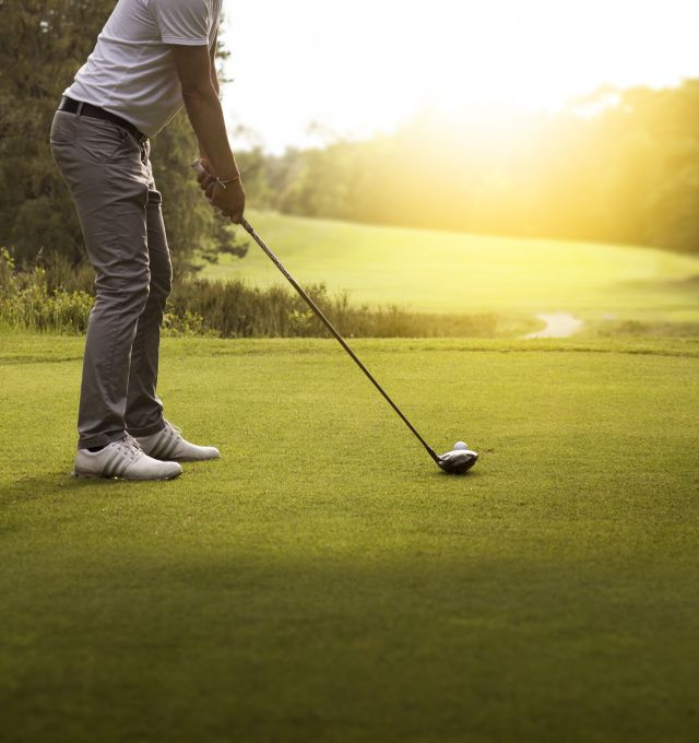 A golfer stands in position to tee off.
