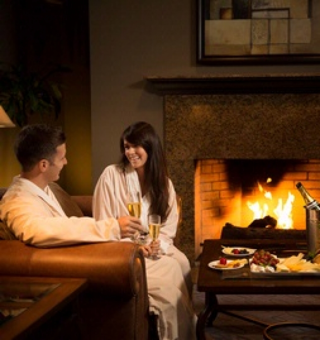 Couple in robes chatting by a fire