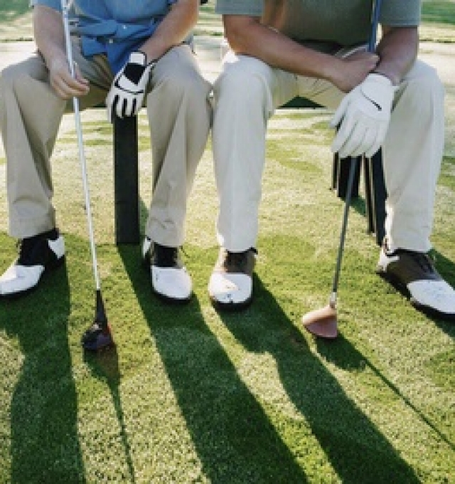 Two golfers sitting on a bench