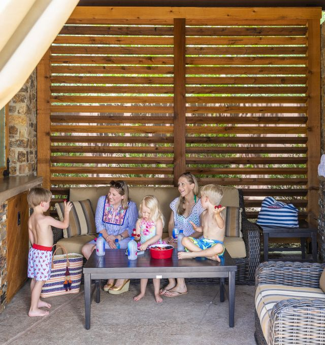 two moms and kids sitting in an outdoor cabana