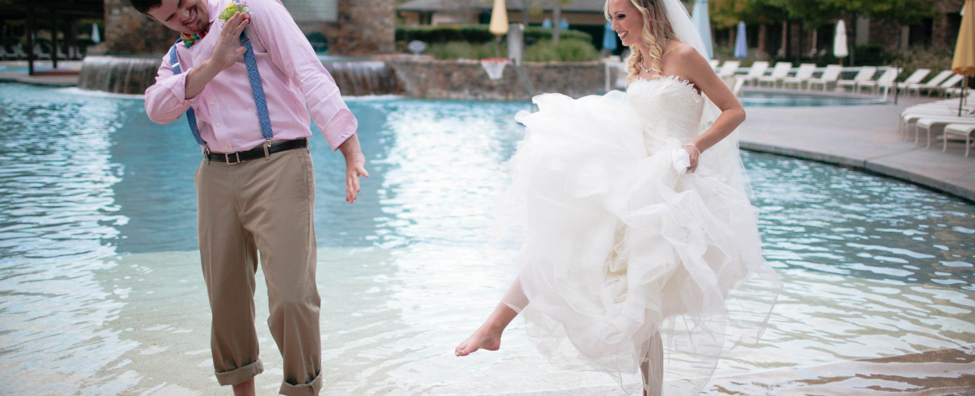 A bride and groom play by the pool side.