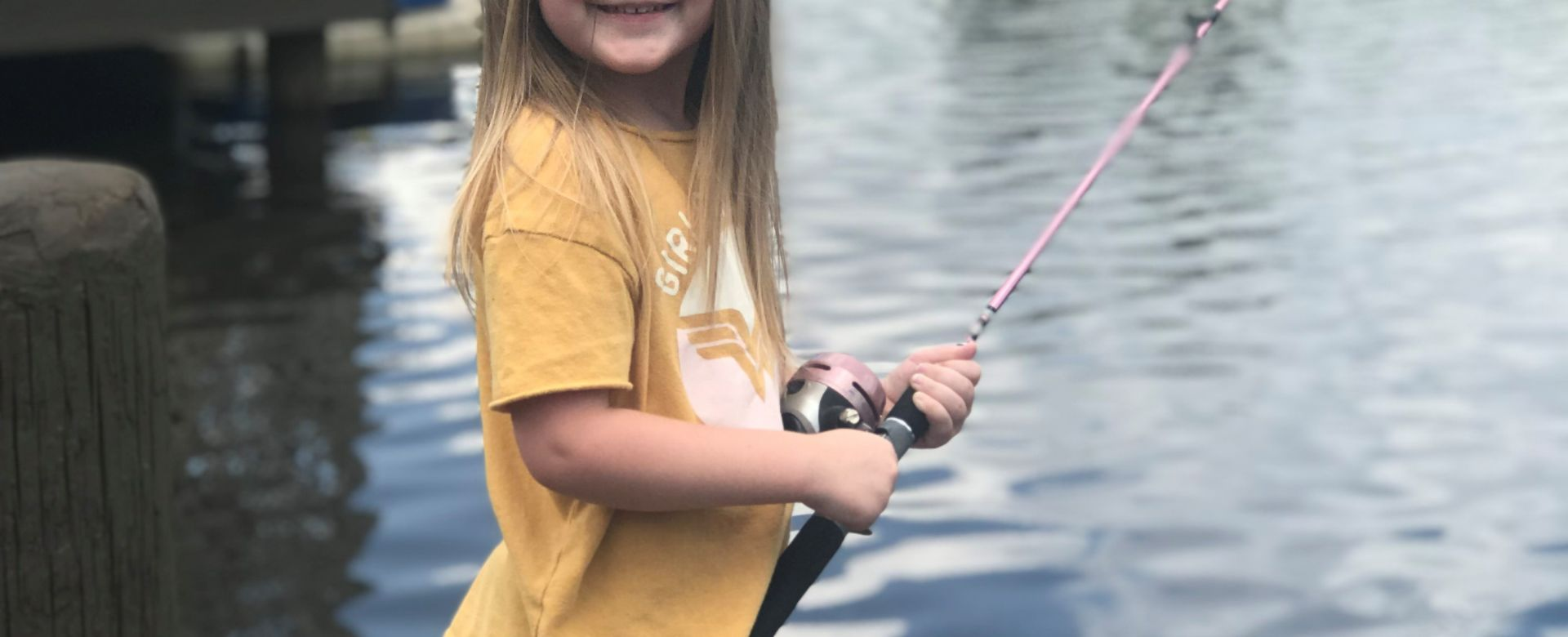 little girl fishing in a lake